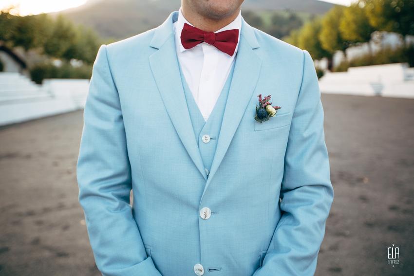 Boutonniere du marié, costume bleu ciel et noeud papillon rouge